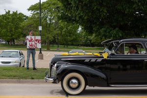 """Dean Rodney Miller drives a classic car through campus, and a young man standing on the sidewalk holds a sign that says """"We Love You."""""""