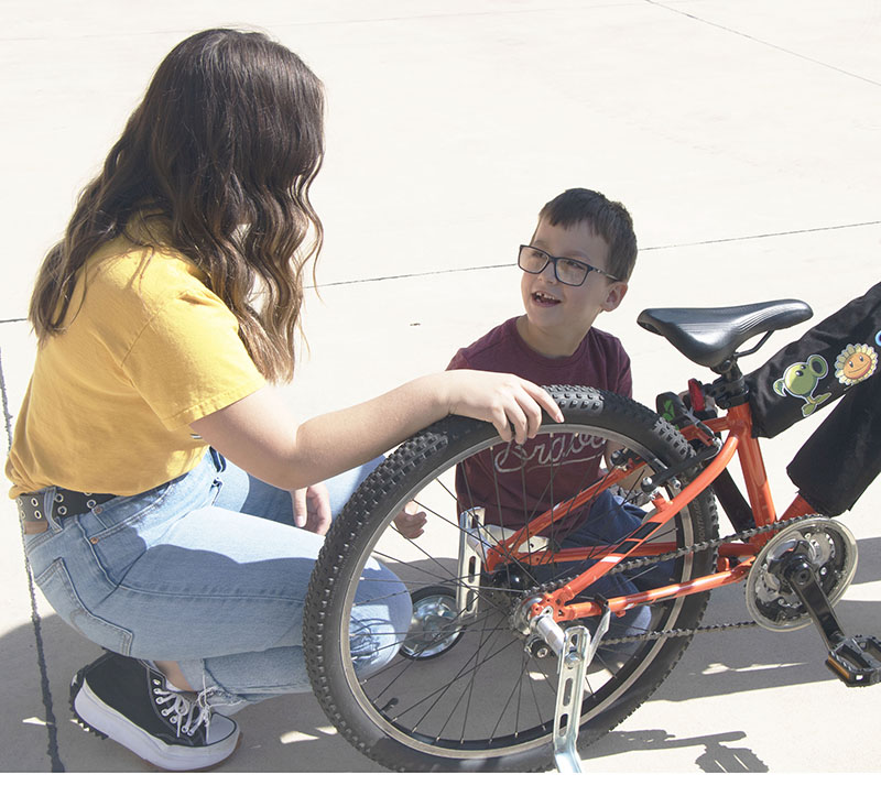 Ford Hall speaks with Adrianna Gutierrez as he inspects his new bike.