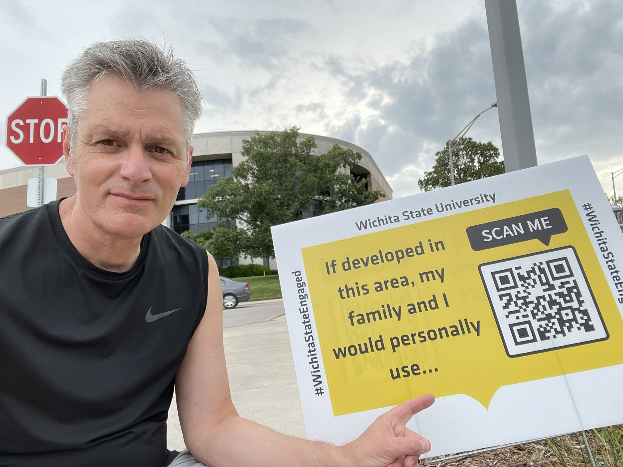 """WSU president Dr. Rick Muma poses with a sign that reads """"If developed in this area, my family and i would personally use ... """" There's also a QR Code and the words """"Scan Me."""""""