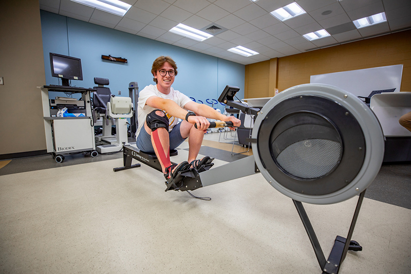 Gianluca Gabriele operating and posing on a rowing machine.