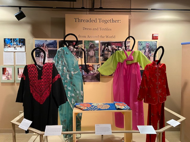 """This photos shows part of an exhibit entitled """"Journey Around the World"""" created by the 2019 Spring Exhibition Class. It shows traditional clothing from Asia."""