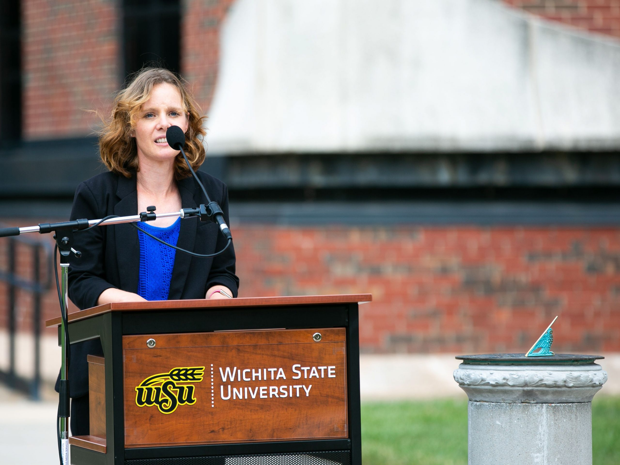 Morgan Barnes, professional services manager for the Public Policy and Management Center, speaks at the rededication ceremony for a sundial that was donated to Wichita State in 1934. The sundial was dedicated to the late Dr. George Platt, professor emeritus at the Hugo Wall School of Public Affairs, and is located on the east side of Hubbard Hall.