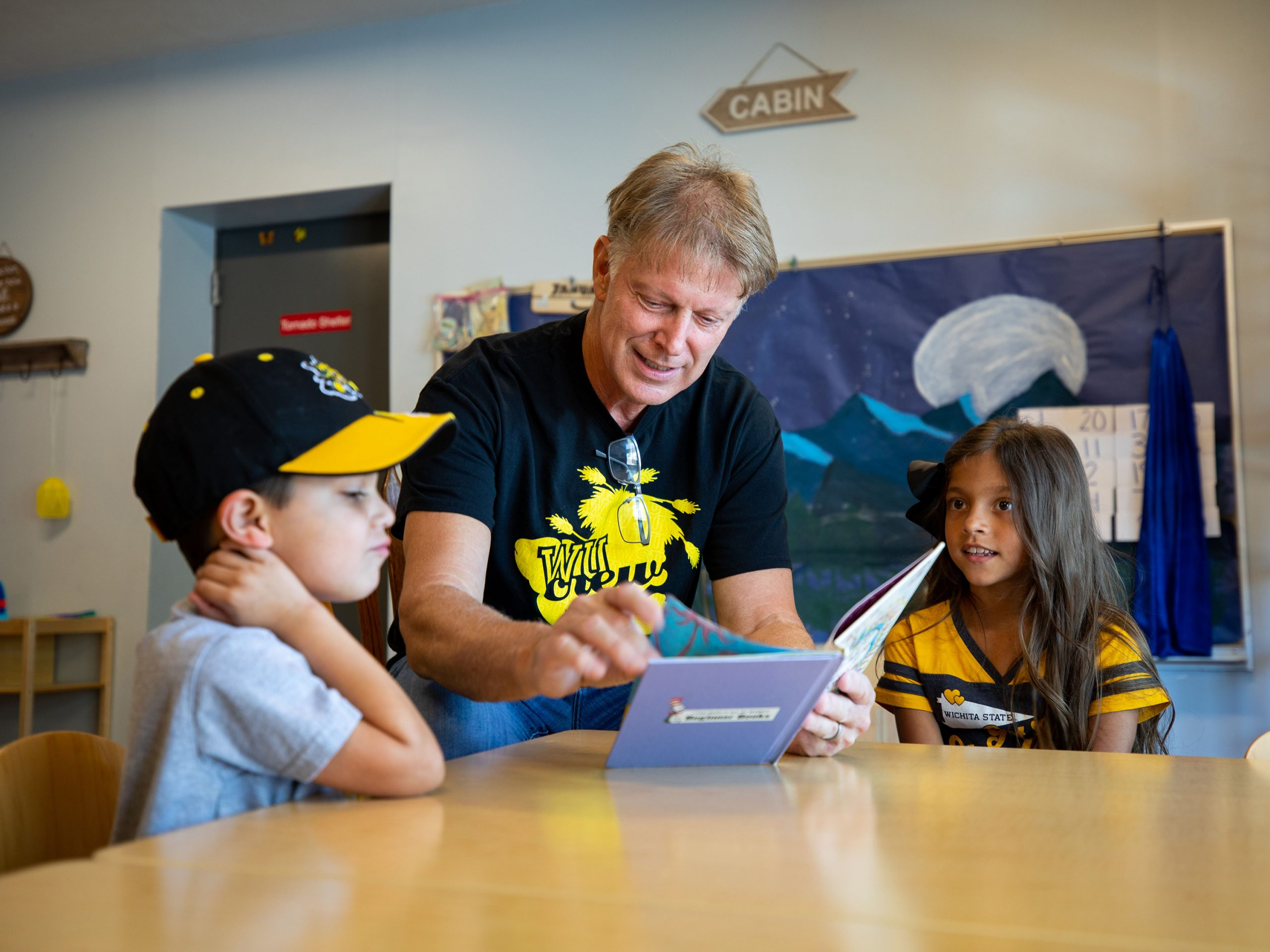 First gentleman Rick Case reads a book to two children as a volunteer for Wu Crew Reads.