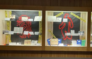 """The images showes the exhibit """"Crime Scene ICT"""" It is three different display cases with 2 glass shelves in each case with documents and photographs about the history of Forensic Science in Wichita. The backgound of each case is black with a large red """"crime scene"""" related inmage in each. The first case on the black background is a red fingerprint. In the middle case on the black background is a red outline of a person. On the third case on the black background is a red microscope and vial. Each case has yellow crime scene tape that says """"Crime Scene Do Not Cross."""""""