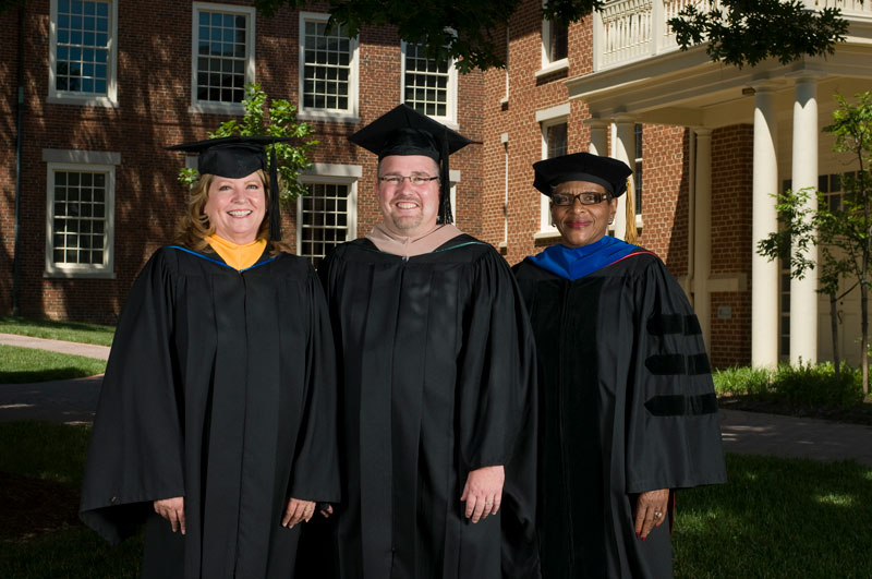 Picture of Faculty/staff members standing in front of a building wearing regalia.