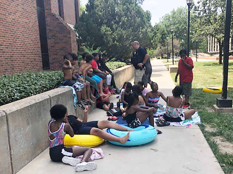 A Wichita State police officer visits with local children before their swim lessons.