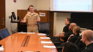 LCDR Joseph M. Hatfield speaks to a roomful of people
