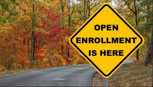 Yellow sign on side of road featuring text 'Open Enrollment is here.'