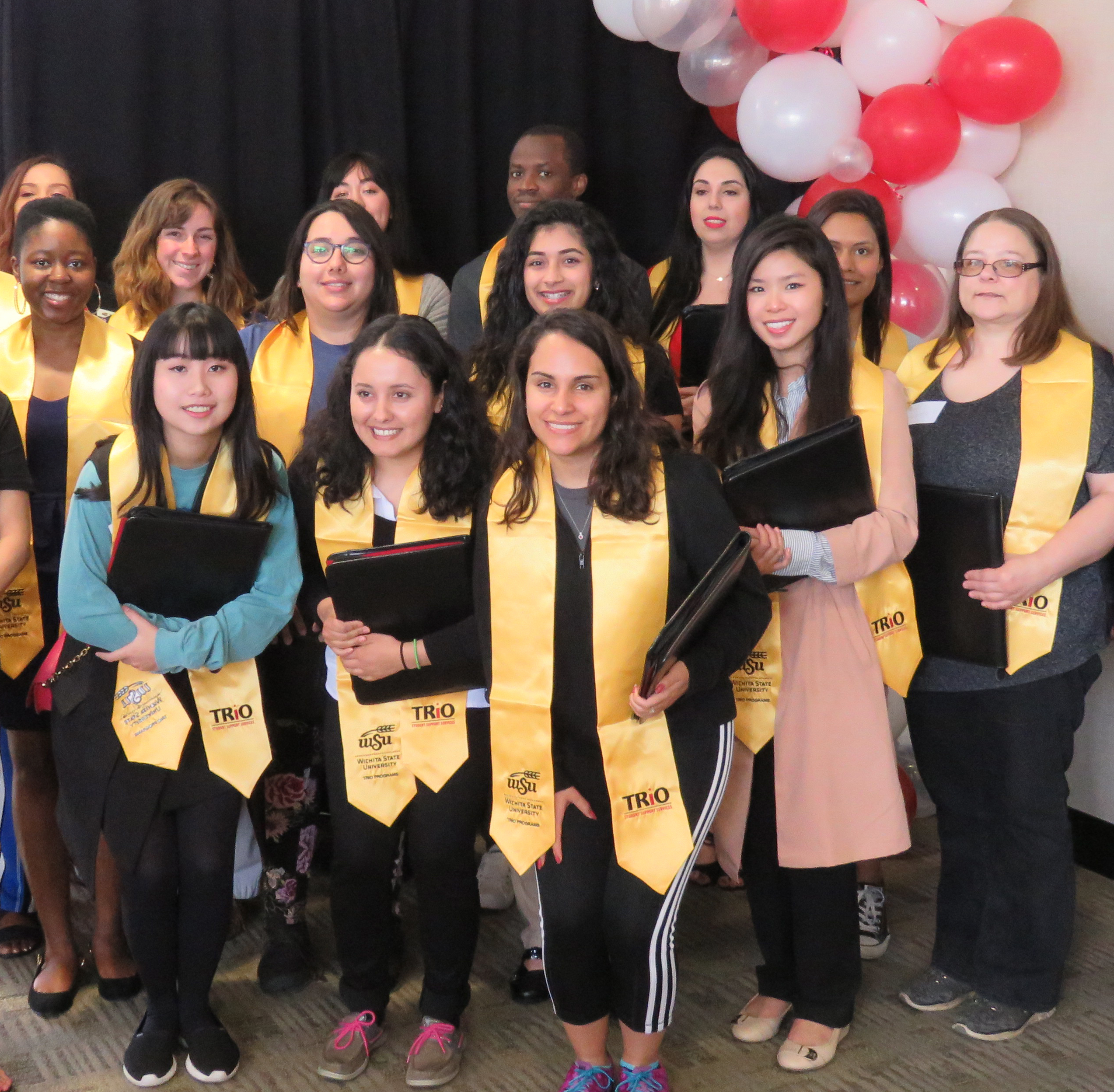 Several TRIO Student Support Services graduates gather for a group photo wearing their TRIO stoles and holding their graduate ceremony gift of a zippered pleather portfolio with big smiles.