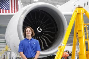 Picture of Wichita State senior Preston Keasey, majoring in mechanical engineering, in front of jet engine.